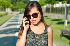 Jong mooi meisje die bij telefoon buiten in park spreken Stock Fotografie