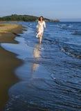 Jong mooi meisje die bij Th-kust wandelen Stock Afbeeldingen
