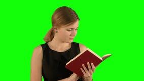 Jong mooi meisje die een boek op laptop op a lezen stock videobeelden