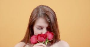 Jong mooi meisje die een boeket van rozen ruiken stock video