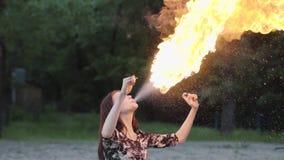 Jong mooi meisje die een show met vlam uitvoeren die zich voor het bos Bekwame fireshowkunstenaar uitademen bevinden stock videobeelden