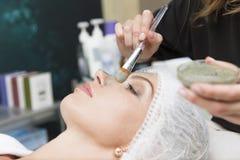 Jong mooi meisje die gezichtsmasker in de salon van de kuuroordschoonheid van cosmetologist ontvangen royalty-vrije stock afbeeldingen