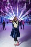 Jong mooi meisje die op de ijs binnen ijsbaan schaatsen Stock Afbeeldingen