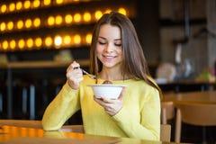 Jong mooi meisje die roomijs in koffie eten royalty-vrije stock afbeelding