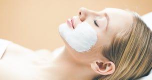 Jong mooi meisje die roze gezichtsmasker in de salon van de kuuroordschoonheid ontvangen royalty-vrije stock afbeeldingen