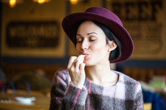 Jong mooi meisje die van frieten in koffie genieten stock foto's