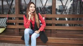 Jong mooi meisje die in vrijetijdskleding op een bank in een stadspark zitten stock video
