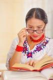 Jong mooi meisje die wit overhemd met kleurrijke bloemdecoratie en glazen dragen, die door het boek te glimlachen van de bureaule Royalty-vrije Stock Fotografie