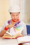 Jong mooi meisje die wit overhemd met kleurrijke bloemdecoratie en het modieuze hoed glimlachen dragen, die door bureau zitten Stock Afbeelding
