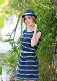 Jong mooi meisje die zich door riverbank bevinden Royalty-vrije Stock Afbeeldingen