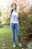Jong mooi meisje die zich onder een boom bevinden stock fotografie