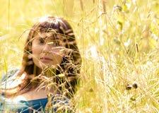 Jong mooi meisje in een gras royalty-vrije stock fotografie
