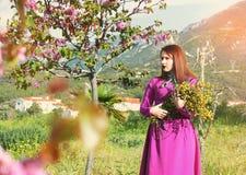 Jong mooi meisje in een heldere roze kleding met een boeket van ye Royalty-vrije Stock Afbeelding