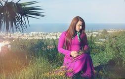 Jong mooi meisje in een heldere roze kleding met een boeket van ye Stock Fotografie