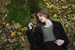 Jong mooi meisje in het midden van de herfstbladeren op de achtergrond stock fotografie