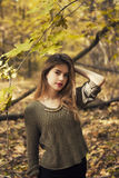 Jong mooi meisje in het midden van de herfstbladeren op de achtergrond stock foto