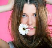 Jong mooi meisje met bloem in haar mond Royalty-vrije Stock Afbeelding