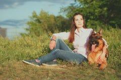 Jong mooi meisje met een Duitse herder die op het gazon spelen Royalty-vrije Stock Afbeelding
