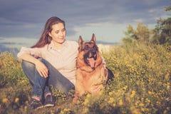 Jong mooi meisje met een Duitse herder die op het gazon spelen Stock Foto
