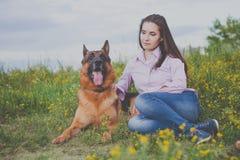 Jong mooi meisje met een Duitse herder die op het gazon spelen Royalty-vrije Stock Fotografie