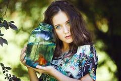 Jong mooi meisje met gouden vissen Stock Afbeelding
