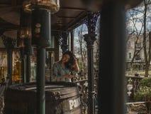 Jong mooi meisje met het spinnen van haar op de straat dichtbij de lantaarns en een groot vat stock afbeeldingen