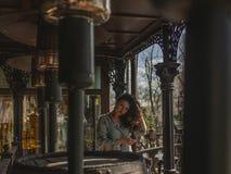 Jong mooi meisje met het spinnen van haar op de straat dichtbij de lantaarns en een groot vat stock afbeelding