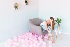 Jong mooi meisje met lang haar in wit hemd en jeans met gaten die in een leunstoel zitten Dichtbij heel wat roze ballons royalty-vrije stock foto's