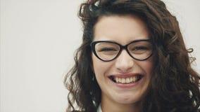 Jong mooi meisje met schitterend haar Op een witte achtergrond Oprecht gekleed in glazenglimlachen stock videobeelden