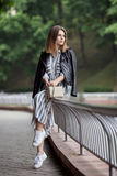 Jong mooi meisje in modieuze streetwear zwarte lange gestreepte de kledings witte tennisschoenen van het leerjasje en met een mod Stock Fotografie