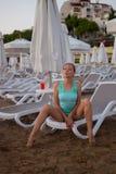 Jong mooi meisje op het strand die uit aan overzees kijken Stock Afbeeldingen