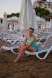 Jong mooi meisje op het strand die uit aan overzees kijken stock fotografie