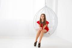 Jong mooi meisje in rode kleding die in een gebied-als decoratieve schommeling rusten Elegante en comfortabele te ontspannen plaa Stock Afbeelding