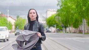 Jong mooi meisje in zwart leerjasje tegen de achtergrond van de stad Het houden van een grijze sjaal Haar die in de winst fladder stock videobeelden