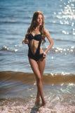 Jong mooi meisje in zwempak het stellen in zeewater stock foto's