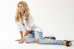 Jong mooi meisjesblonde in een wit overhemd en jeans met hiaten royalty-vrije stock fotografie