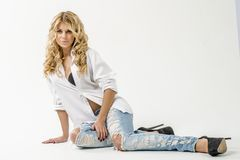 Jong mooi meisjesblonde in een wit overhemd en jeans met hiaten royalty-vrije stock afbeeldingen