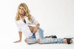 Jong mooi meisjesblonde in een wit overhemd en jeans met hiaten stock fotografie