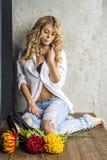 Jong mooi meisjesblonde in een wit overhemd en jeans met hiaten stock foto's
