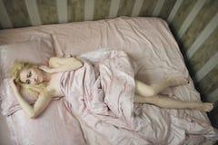 Jong mooi meisjeskielzog omhoog in de ochtend in een bed Stock Foto