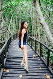 Jong mooi meisjesportret op de houten brug in het mangrovebos Stock Afbeeldingen