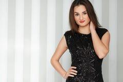 Jong mooi modieus meisje met rode lippen die in verbazende elegante avond zwarte kleding stellen Royalty-vrije Stock Afbeelding