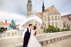 Jong mooi modieus paar jonggehuwden die door het Bastion van de Visser in Boedapest, Hongarije kussen stock foto's