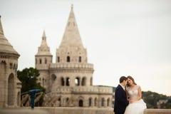 Jong mooi modieus paar jonggehuwden die door het Bastion van de Visser in Boedapest, Hongarije zitten stock afbeelding