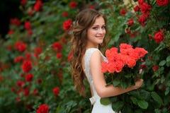 Jong mooi mooi meisje met lang haar en witte kledingstribune Stock Foto's