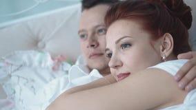 Jong mooi paar die in bed rusten, die de afstand, close-up onderzoeken stock video