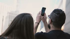 Jong mooi paar die binnen de stad in van Chicago, Amerika en het nemen van foto van wolkenkrabber op smartphone lopen stock videobeelden