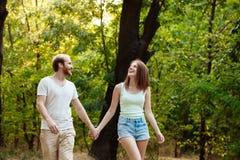 Jong mooi paar die, lopend in park, het glimlachen, het verheugen zich rusten Openlucht achtergrond stock fotografie