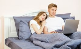 Jong mooi paar die op bed in slaapkamer liggen en laptop met behulp van stock fotografie