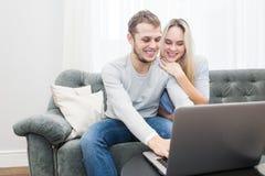 Jong mooi paar die op de laag en het letten op online video van laptop in de woonkamer rusten royalty-vrije stock foto's